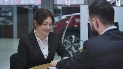 Close-up of Smiling Caucasian Businesswoman Signing Documents in Car Dealership. Happy Female
