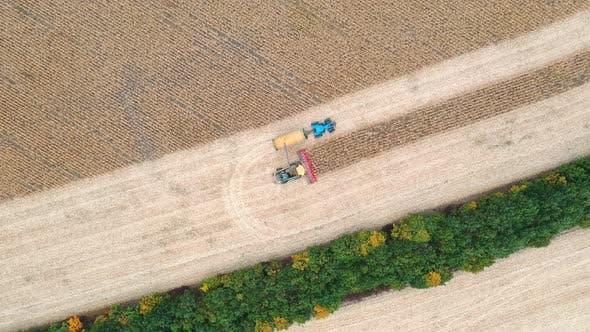 Thumbnail for Luftaufnahme des kombinierten Ladens von Maiskörnern in Traktoranhänger. Fliegen über die Landwirtschaft