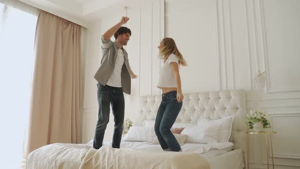 Thumbnail for Slow Motion of Young Married Couple Jumping on Double Bed in Light Room with Large Windows