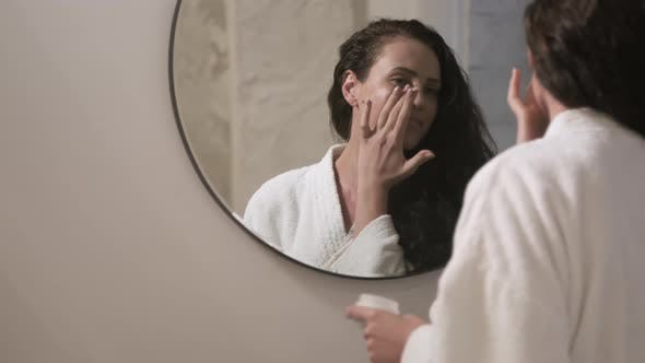 Thumbnail for Happy Woman Applying Cream to Face and Looking in Bathroom Mirror
