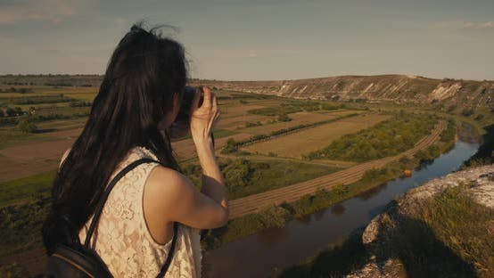 Cover Image for Young female tourist taking a photo of a picturesque canyon in the summer.
