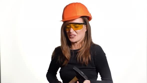 Beautiful Woman in Orange Eyeglasses and Helmet is Holding a Hammer in Her Hands
