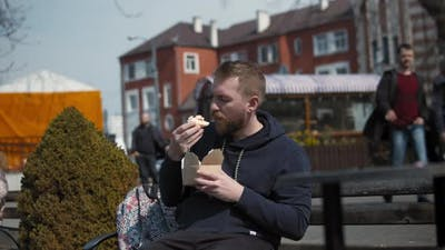 Bearded Young Man Eating Food on the Street