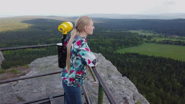 Thumbnail for Woman Looks at a Beautiful View on Top of a Mountain.
