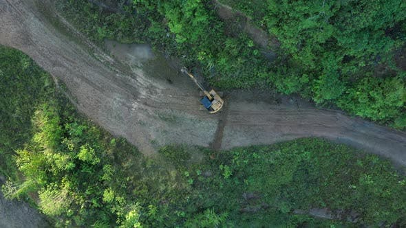Above view of an excavator that is working on the road while zooming out