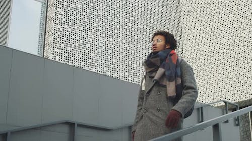 Young Black Man Walking Downstairs in City
