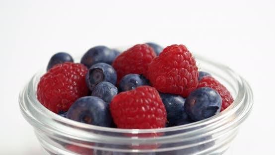 Thumbnail for Raspberries And Blueberries Spinning In White Studio Lightbox Display