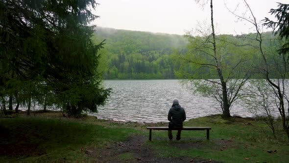 Enigmatic lonely man sitting on bench on lake shore in the mountain forest. Rainy day