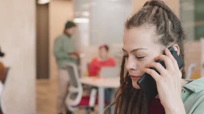 Businesswoman in Dreadlocks Talking on Mobile Phone