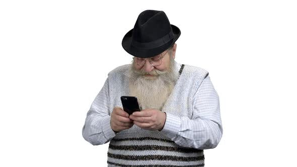 Retired Man with Beard Using Mobile Phone