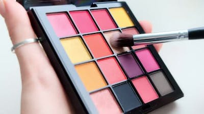 Close up a palette with colorful eye shadows and a makeup brush