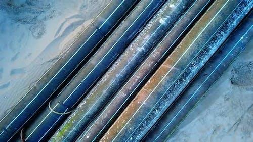 Alte Farbe Kunststoff Drainagerohre liegen auf Sand Sea Beach