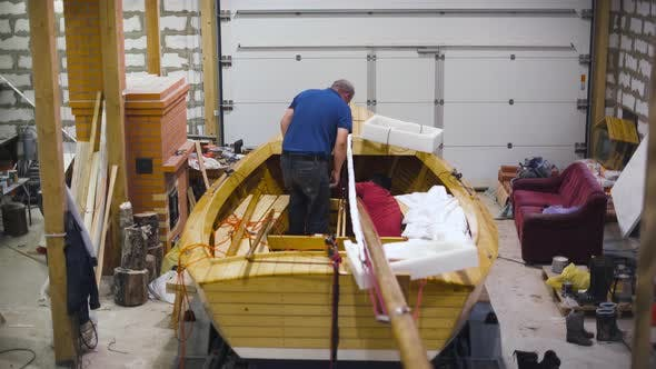 Thumbnail for Master Working with New Wooden Homemade Boat in Workshop. Wide.
