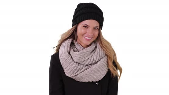 Thumbnail for Smiling portrait of woman in cozy hat and scarf in studio with copyspace