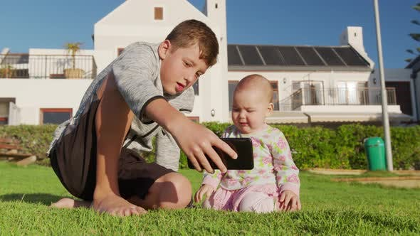 Older Brother Shows Phone To Little Baby Sister Sitting on the Grass