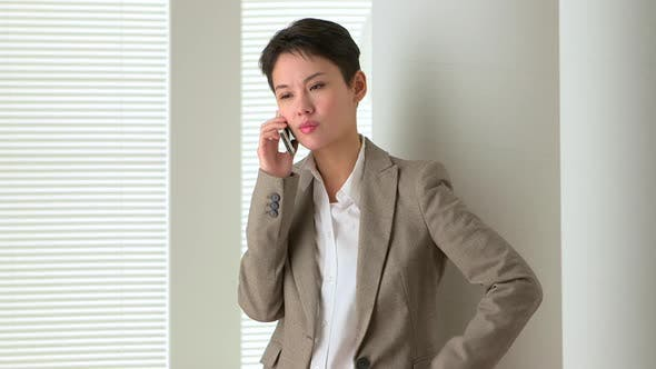 Thumbnail for Unhappy Asian business woman talking on mobile phone