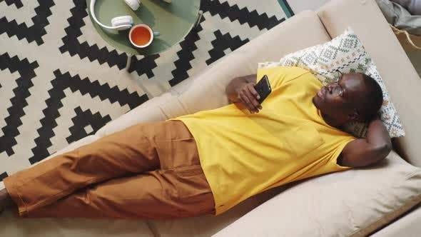 Black Man Resting on Sofa with Smartphone