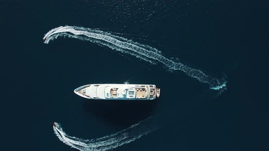 Thumbnail for Aerial view of two Jet Ski Zooming heart around Super Yacht at Sunset. Heart round the super yacht