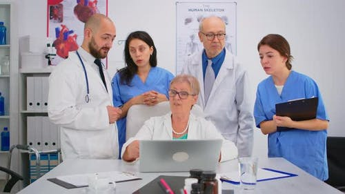 Doctors in Lab Coats Working in Hospital Office Discussing Symptoms of Disease