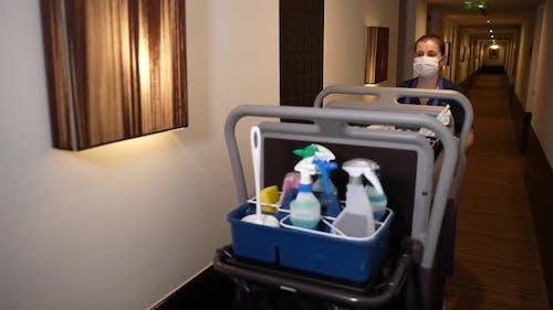 Housemaid with Trolley Walking Down Hotel Corridor