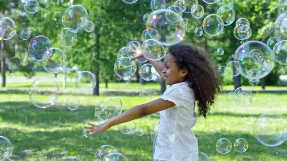 Cover Image for Little Girl and Boy Catching Soap Bubbles while Playing Outdoor