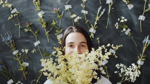 Portrait of Beautiful Woman Holding Meadow Flowers