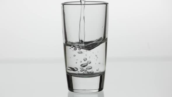Thumbnail for Pouring Up Shot of Vodka Into Drinking Glass. Slow Motion. White Background