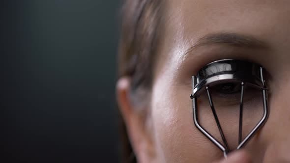 Thumbnail for Woman Corrects Eyelashes with Curling Tongs, Close Up