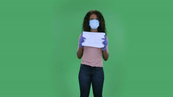 Thumbnail for Portrait of Beautiful African American Young Woman in Medical Mask Is Looking at Camera and Holding