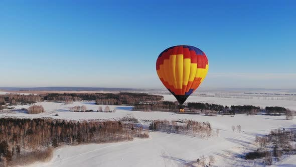 Thumbnail for Aerial Shot of the People Fly on a Big Bright Balloon Over the Winter Forest.