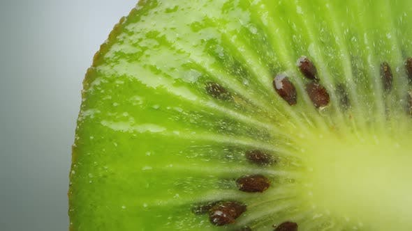 Thumbnail for Macro of kiwi cut in half with seeds and juices shining