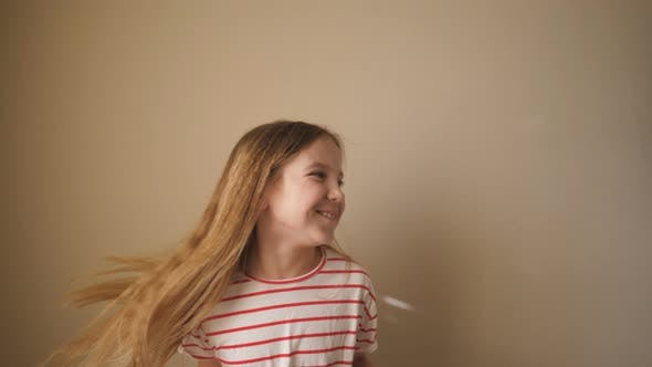 Thumbnail for Happy Smiling Blonde Girl Dancing Funny Against the Background of Wall. Cheerful Small Female Kid
