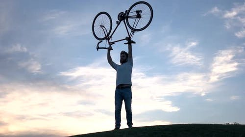 Young Man Lifting Bicycle Above Head