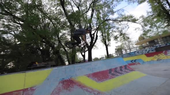 Thumbnail for A young man rides a BMX bicycle in a concrete skate park.
