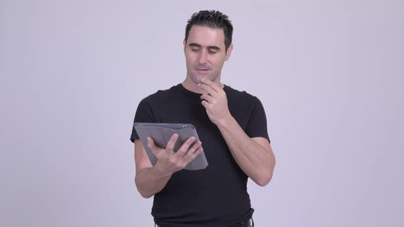 Thumbnail for Handsome Man Thinking While Using Digital Tablet Against White Background