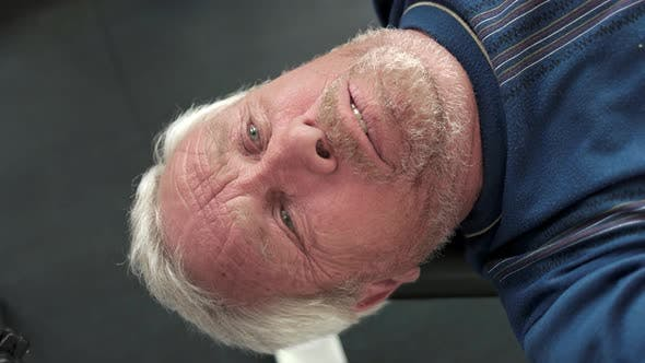 Face of Elderly Man Lifting Weights.
