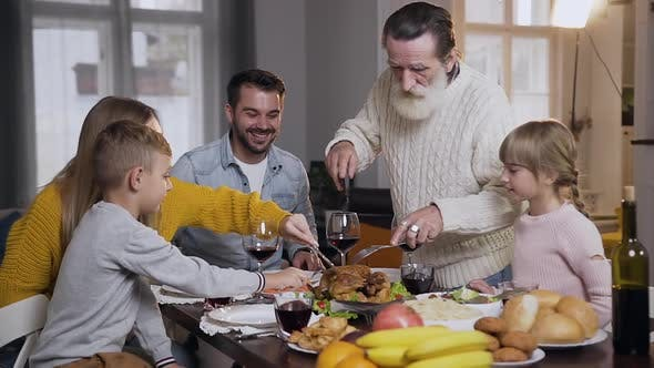 Thumbnail for Respected Senior Grandfather Carving Traditional Roast Turkey