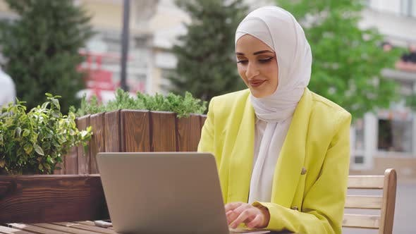 Smiling Young Muslim Woman Wearing Headscarf Sits in Cafe and Uses Laptop