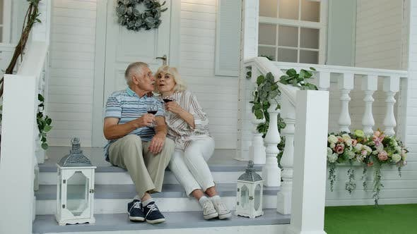 Thumbnail for Attractive Senior Elderly Caucasian Couple Sitting and Drinking Wine in Porch at Home, Making a Kiss