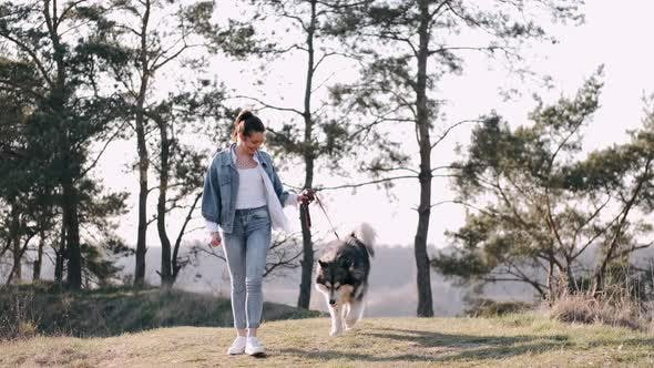 Thumbnail for Pretty Girl Is Walking with a Cute Fluffy Dog in the Field