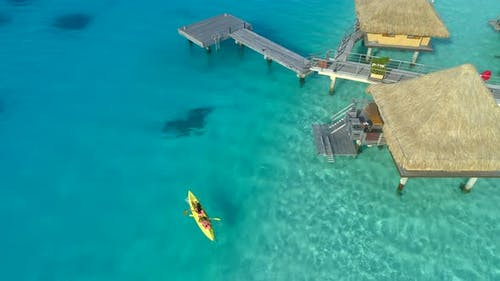 Aerial drone view of a man and woman couple on a tandem sea kayak in Bora Bora tropical island.