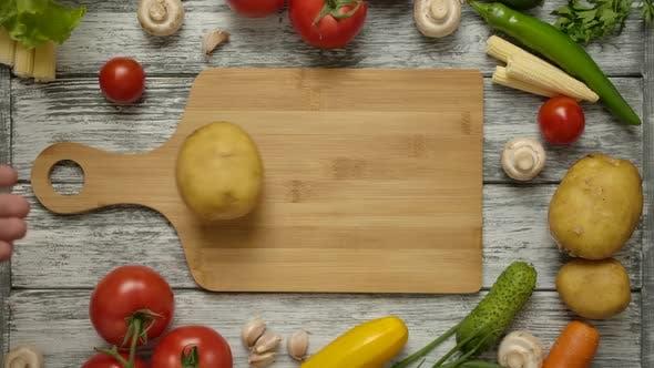 Thumbnail for Kartoffelfrucht-Rollen entlang eines Schneidebretts auf einem Küchentisch mit Gemüse.