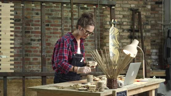 Cover Image for Young Pretty Hipster Paints her Rustic Wooden Toys