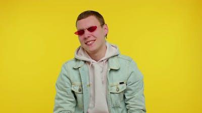 Seductive Cheerful Stylish Man in Denim Jacket Wearing Sunglasses Charming Smile on Yellow Wall