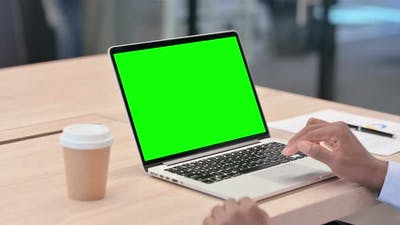 African Businessman Using Laptop with Green Screen