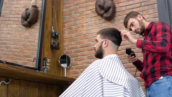 A Man Gets a Haircut in a Stylish Barbershop
