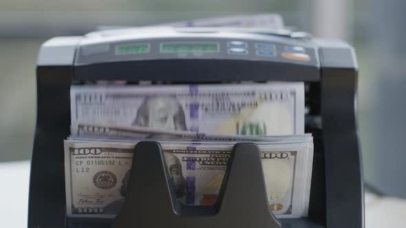 Closeup shot of money counting machine with 100 dollar bills.