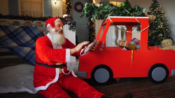 Thumbnail for Joyous Santa Claus Enjoying with Modern Gadget.