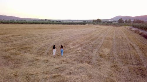 Aerial view two girls walking in the country at sunset