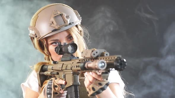 Heavily Armed Female Soldier in Battle Helmet Holding Assault Rifle. Slow Motion